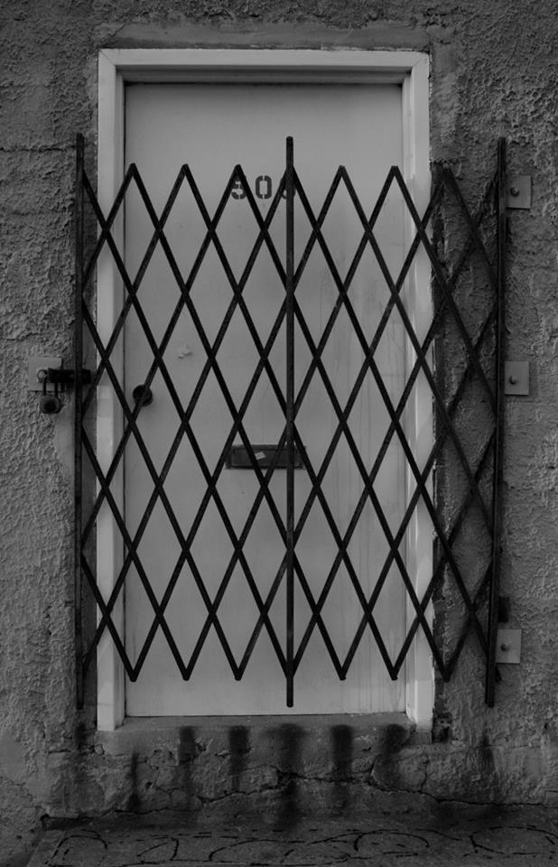 Black and white photograph of an abandoned gated door in NYC