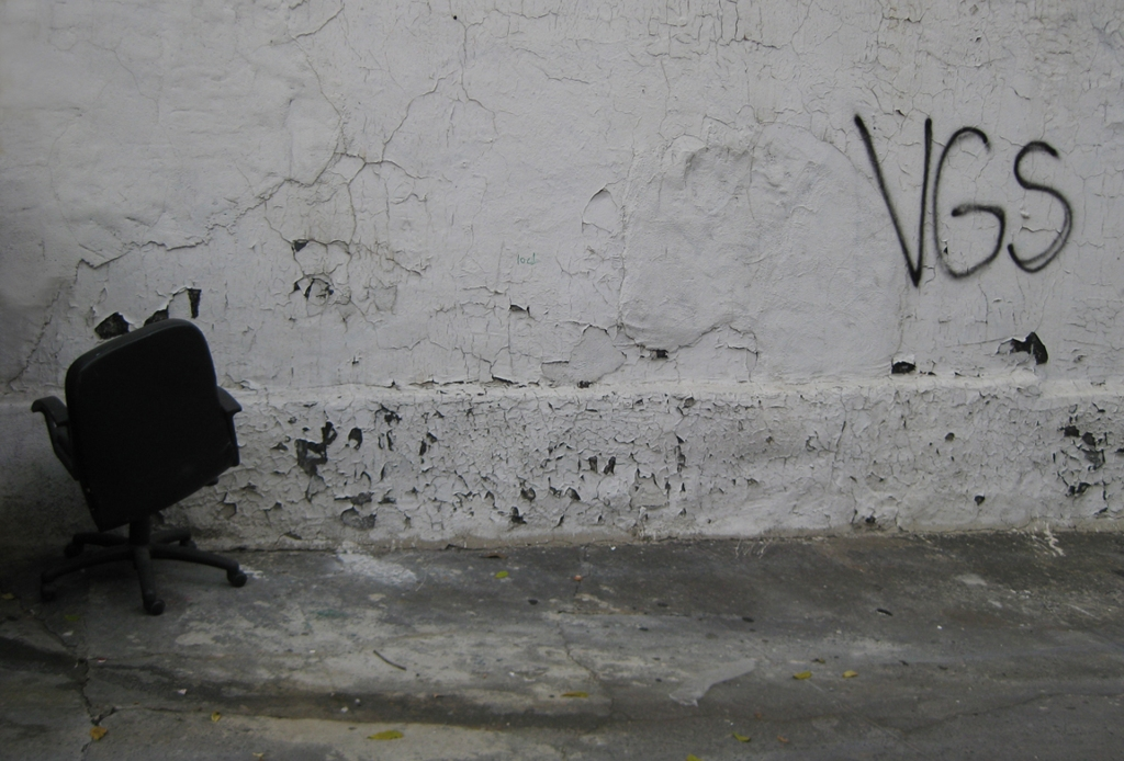 Black and white photo of an office chair in NYC next to simple graffiti