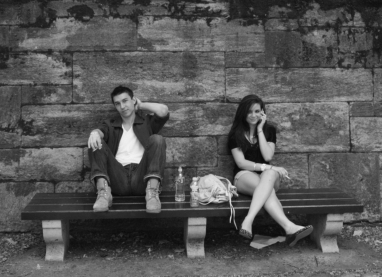Couple at Central Park in NYC sitting on a bench smoking cigarettes and drinking water